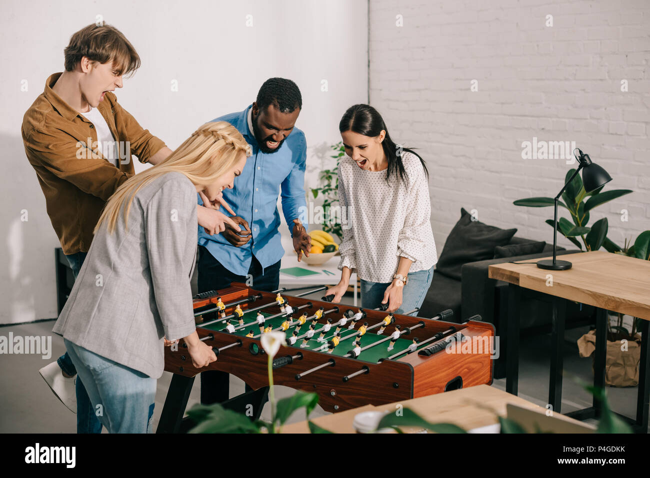 businesswomen playing table football and two male colleagues pointing on  board game - Stock Image 8f958a3b30