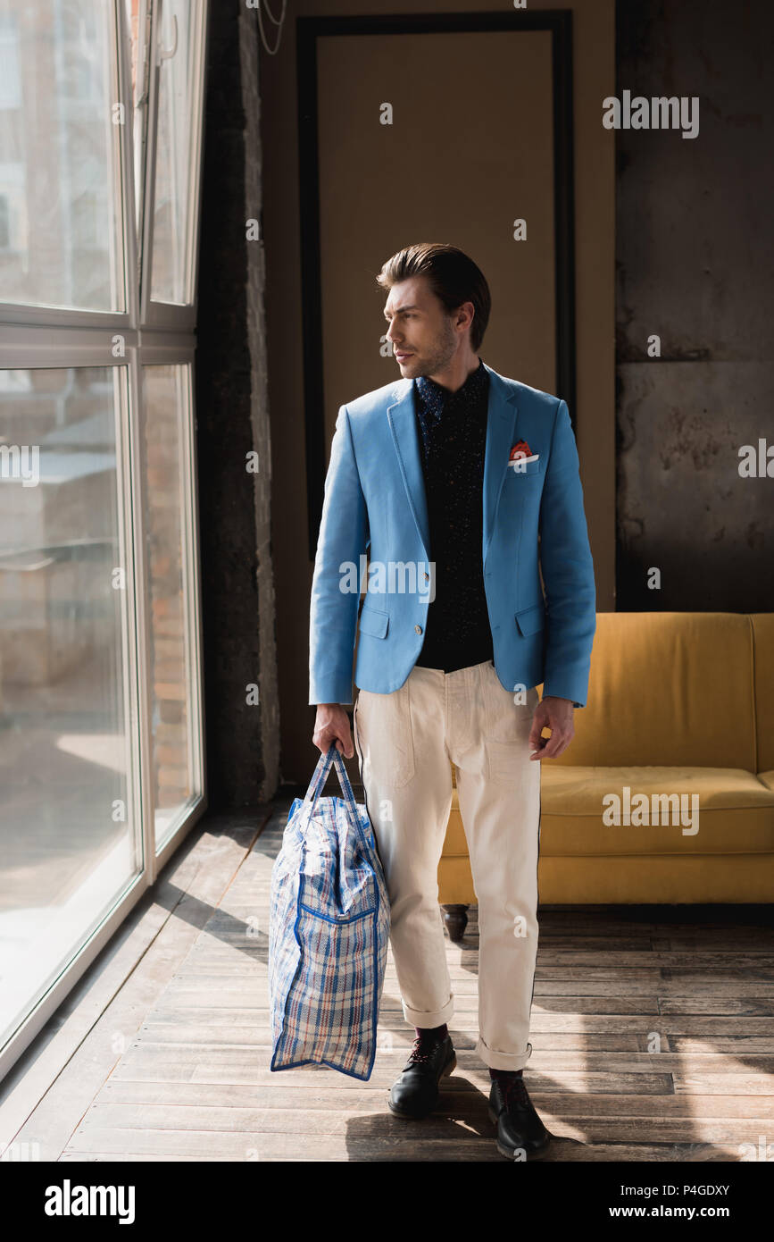 handsome young man with vintage zippered duffle bag - Stock Image