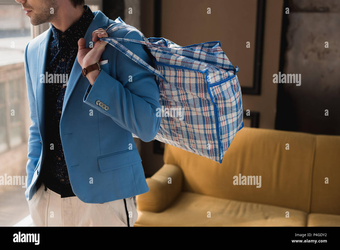 cropped shot of young man with vintage zippered duffle bag - Stock Image