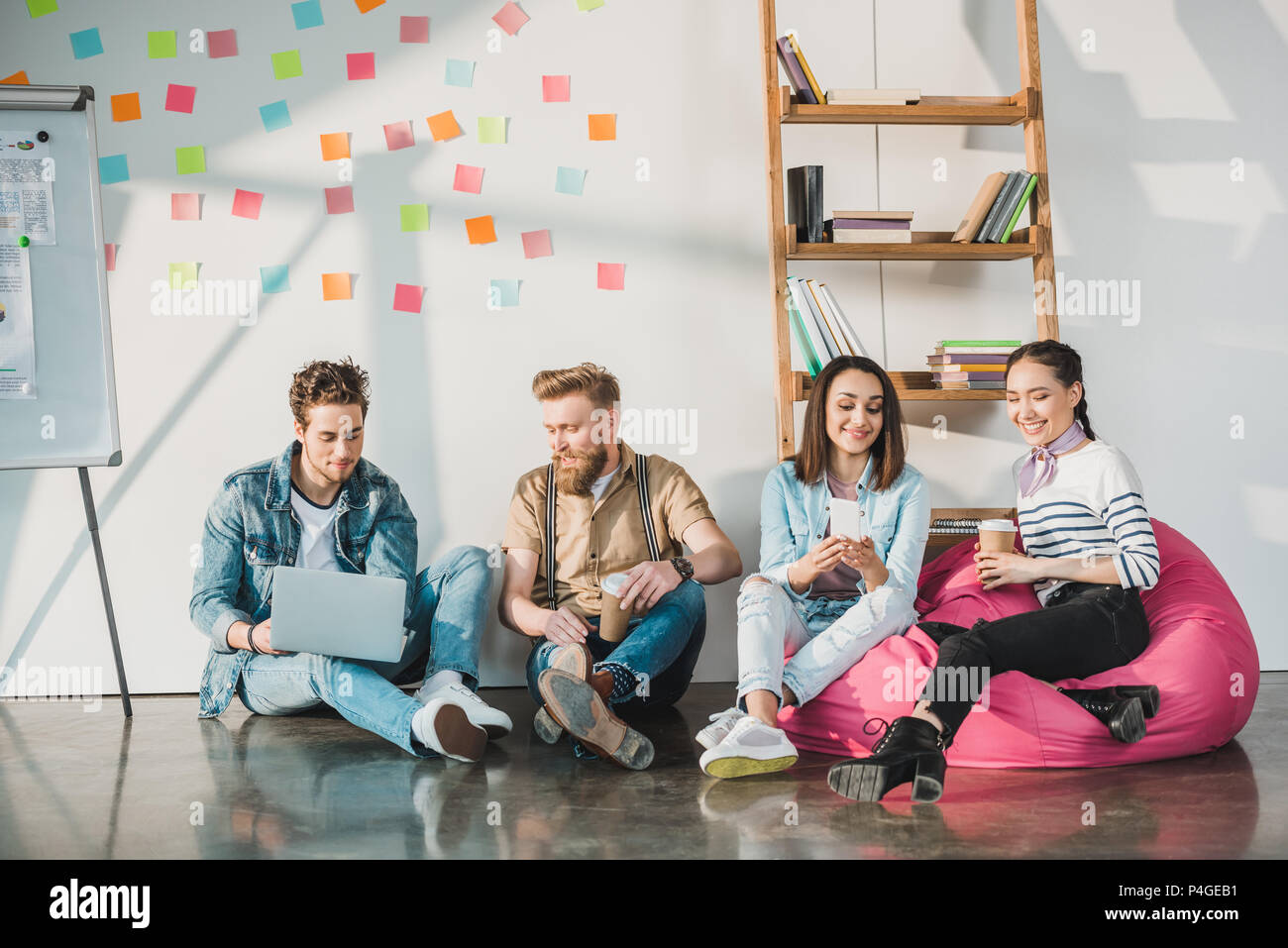 Successful business people discussing decisions by white board with sticky notes in modern light office - Stock Image