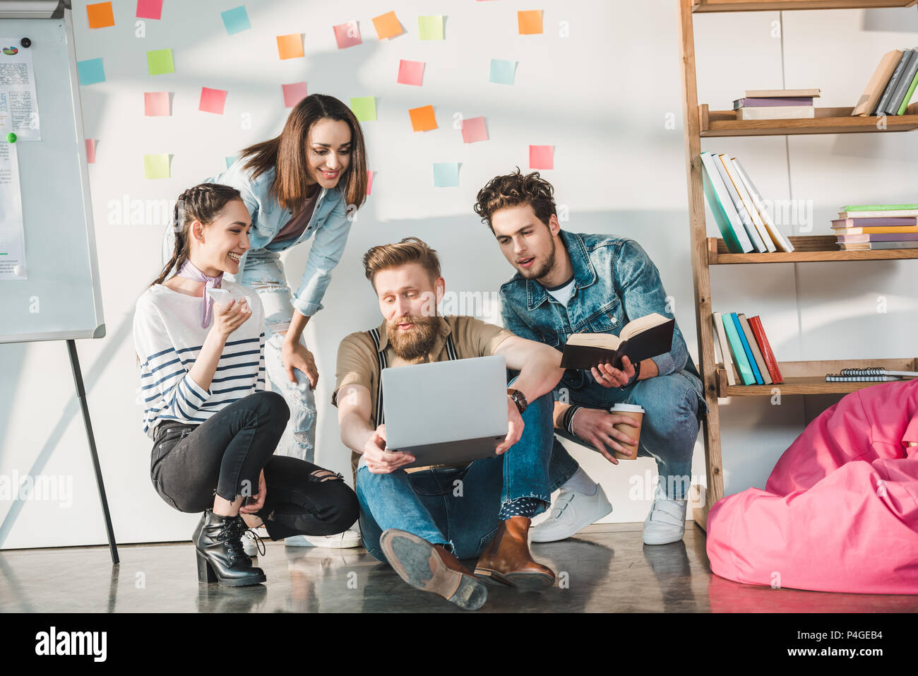 Diverse business team researching ideas in light workspace - Stock Image