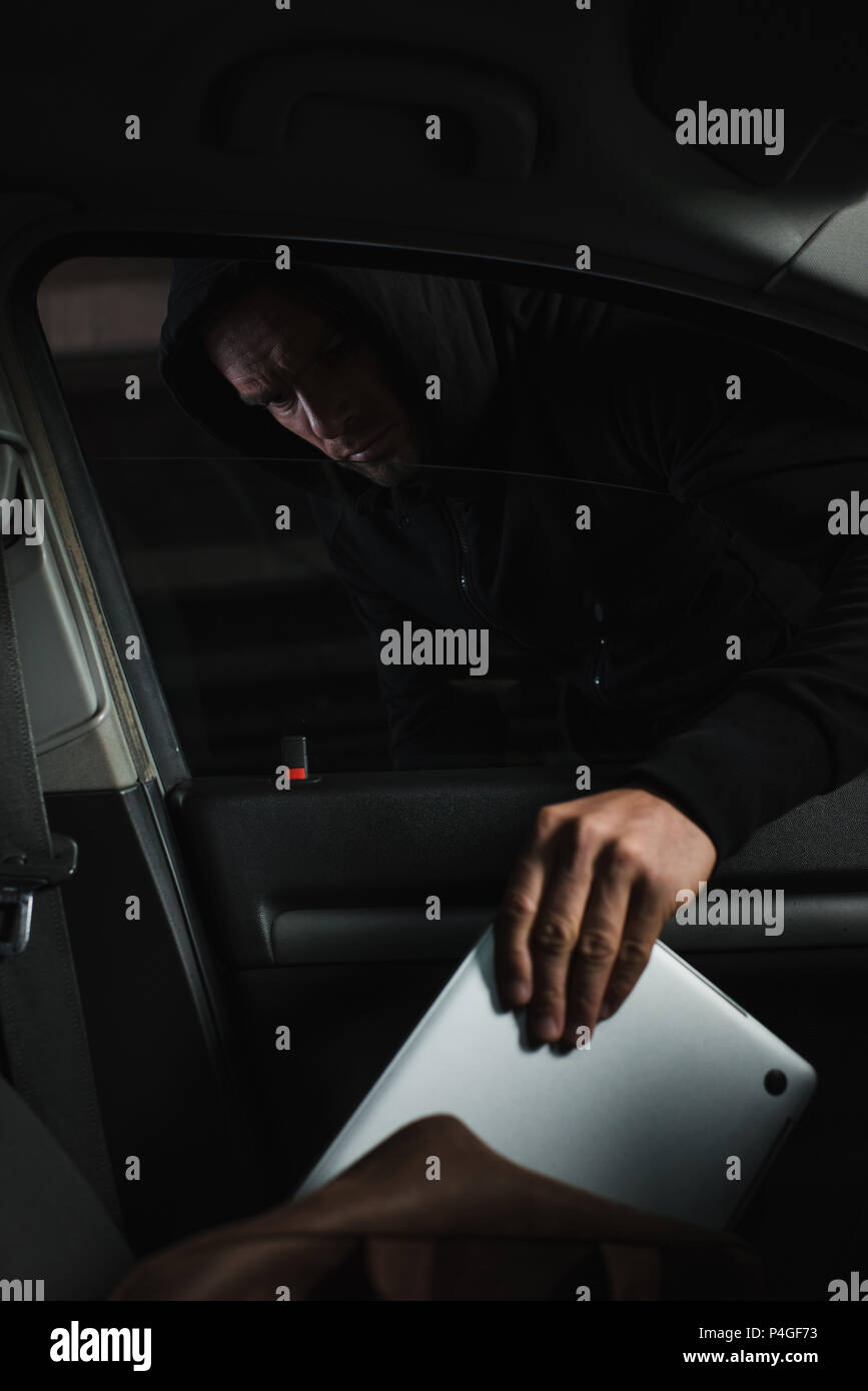 male mugger in black hoodie stealing laptop from case in car - Stock Image