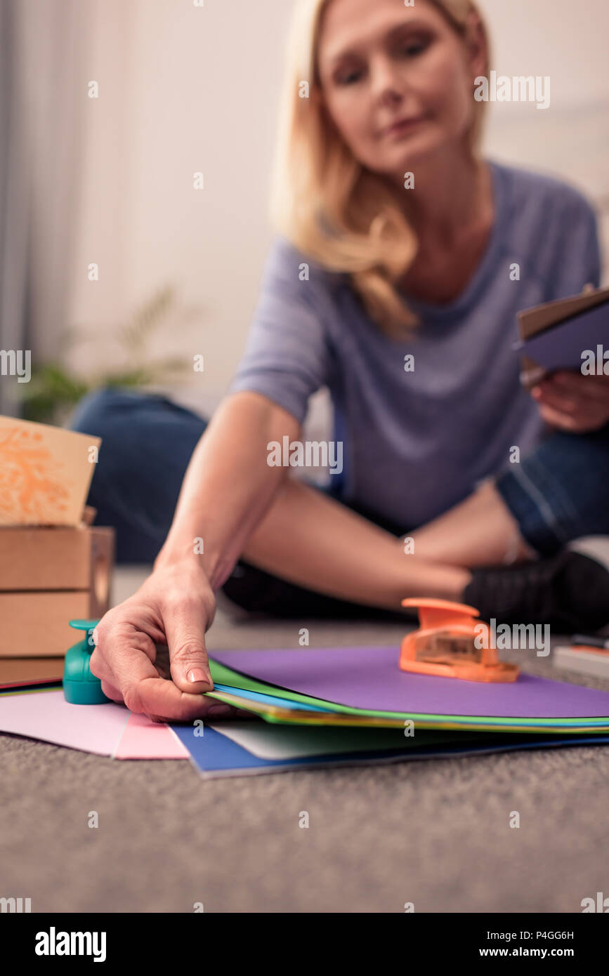 close-up view of blonde woman paper crafting at home - Stock Image