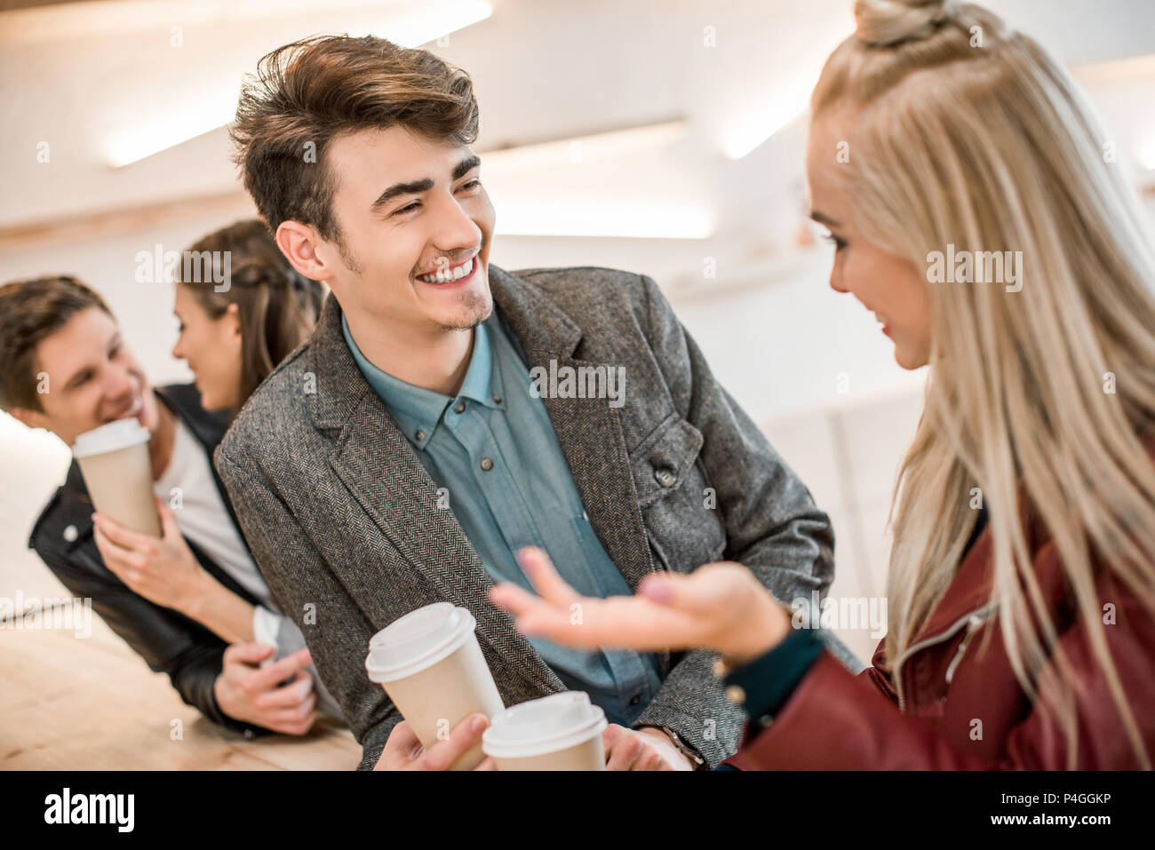 Two heterosexual couples talking at the wooden bar counter - Stock Image