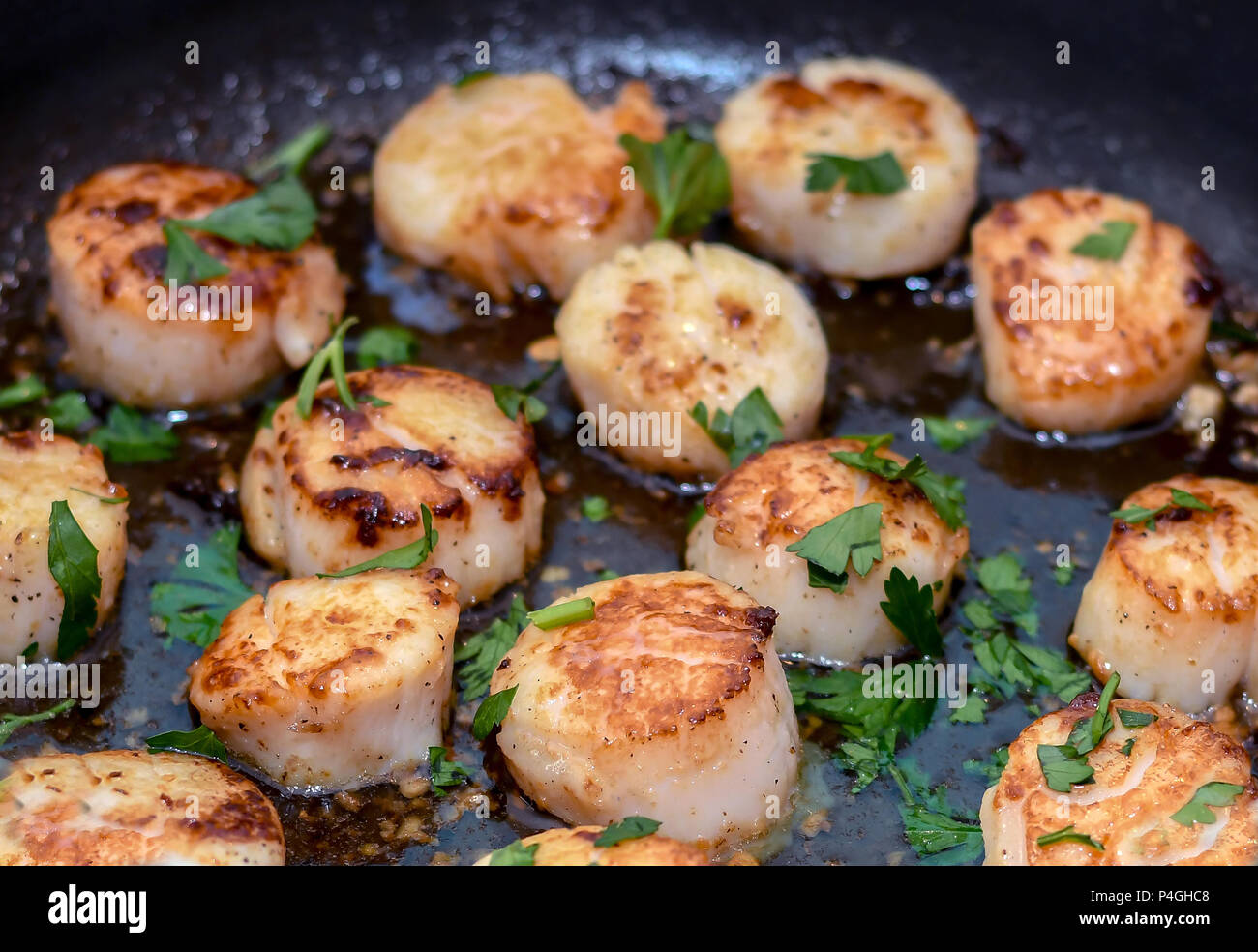 Delectable scallops in a garlic and lemon butter sauce - Stock Image