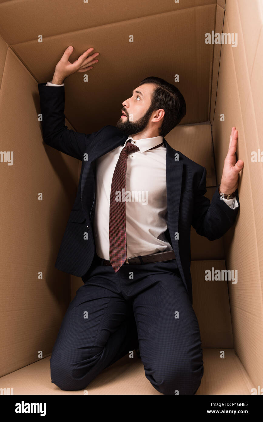 businessman with claustrophobia kneeling in cardboard box - Stock Image
