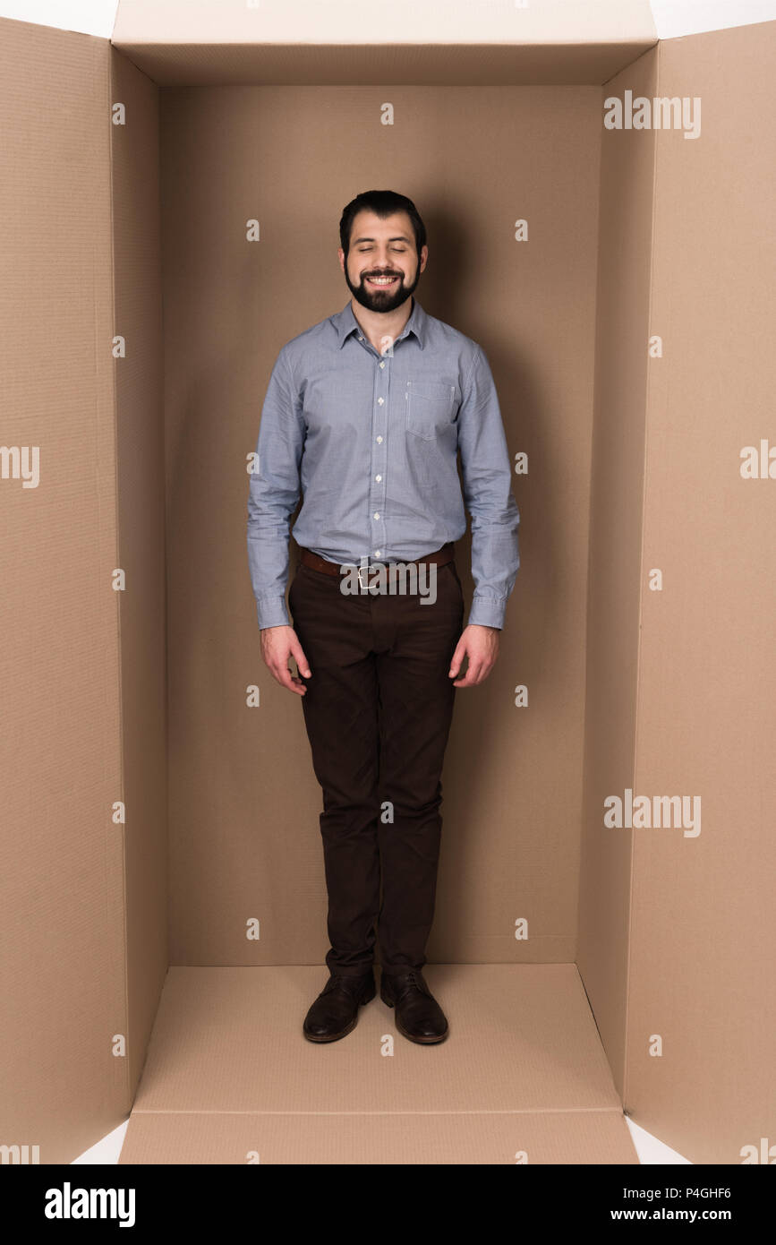 smiling man standing in cardboard box, introvert concept - Stock Image
