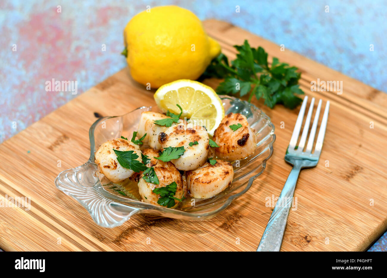 Glass plate of yummy Sea scallops with lemon butter - Stock Image