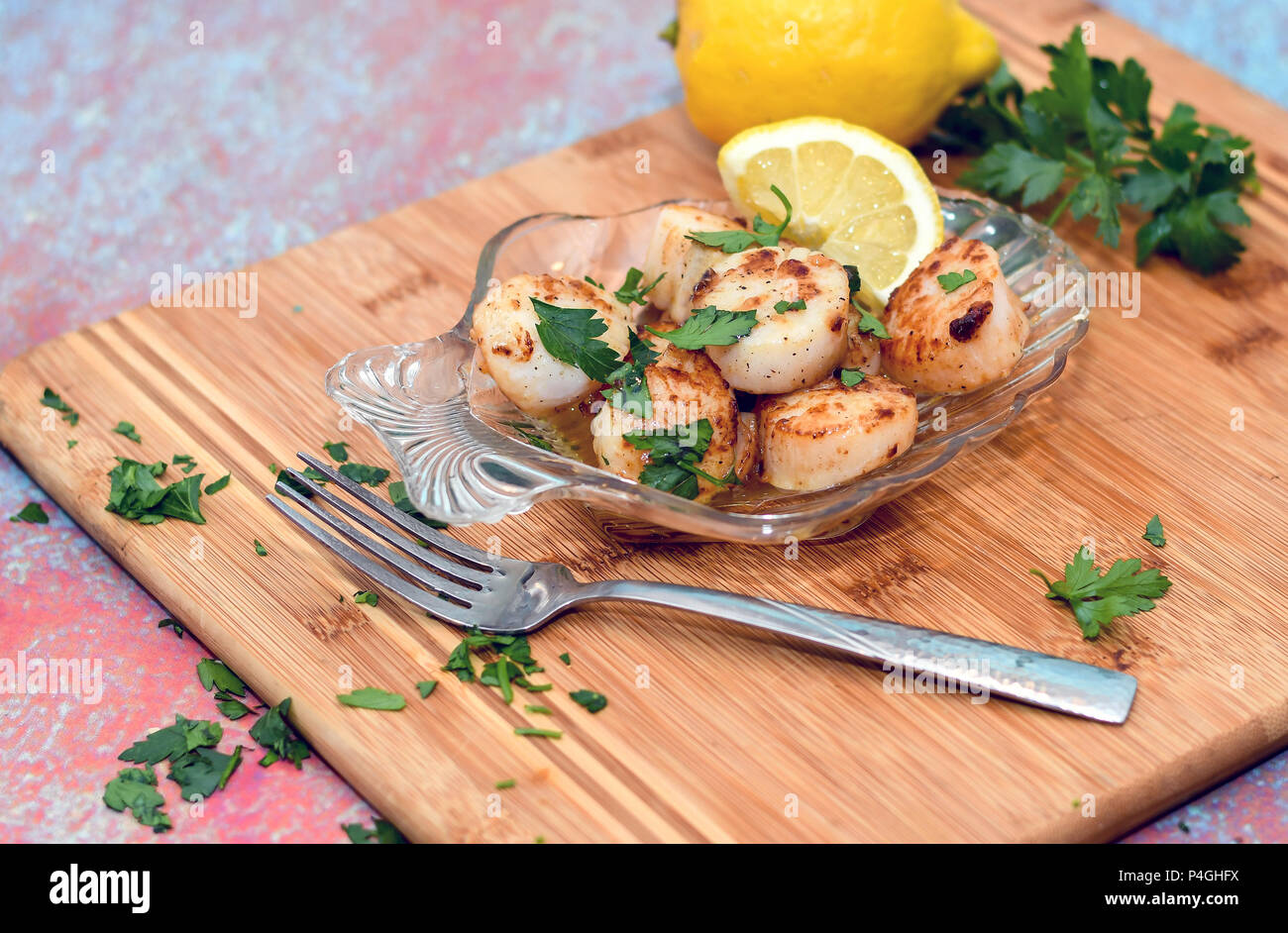 Glass shell plate filled with seared scallops - Stock Image
