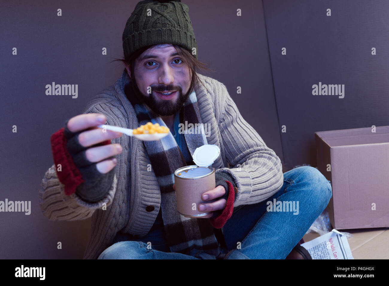 3b33ed21cd5 smiling homeless man eating canned food in cardboard box - Stock Image