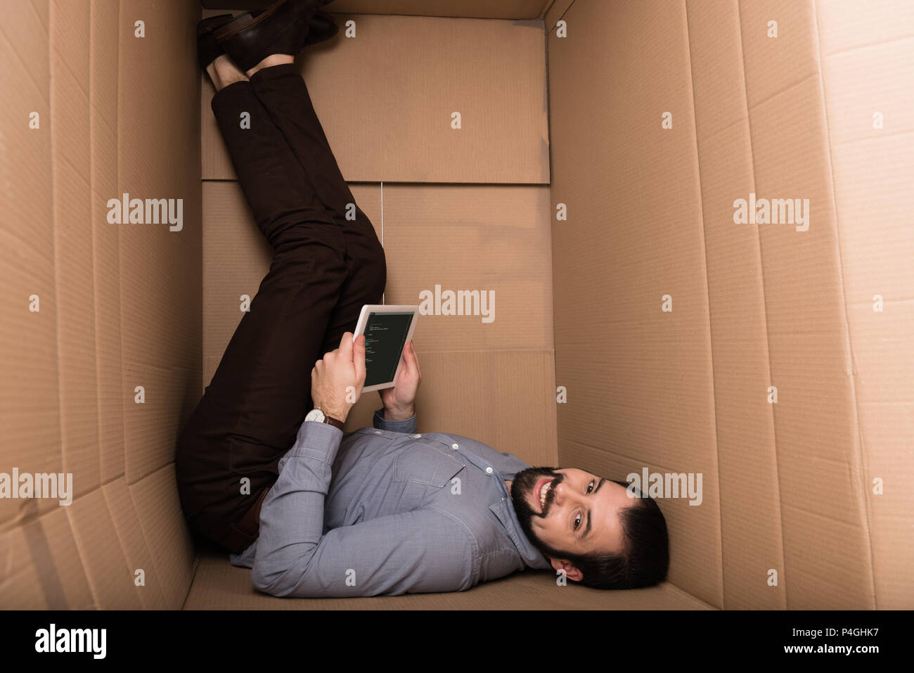 introvert using digital tablet with html code in cardboard box - Stock Image