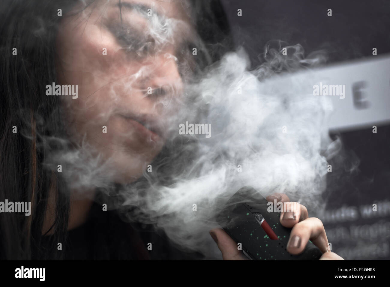 A woman vapes for a photo during Jakarta Vape Fest 2018 in South Jakarta, 6 May 2018. - Stock Image