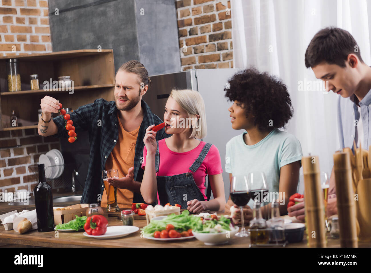 multiethnic friends tasting some food while cooking in kitchen - Stock Image