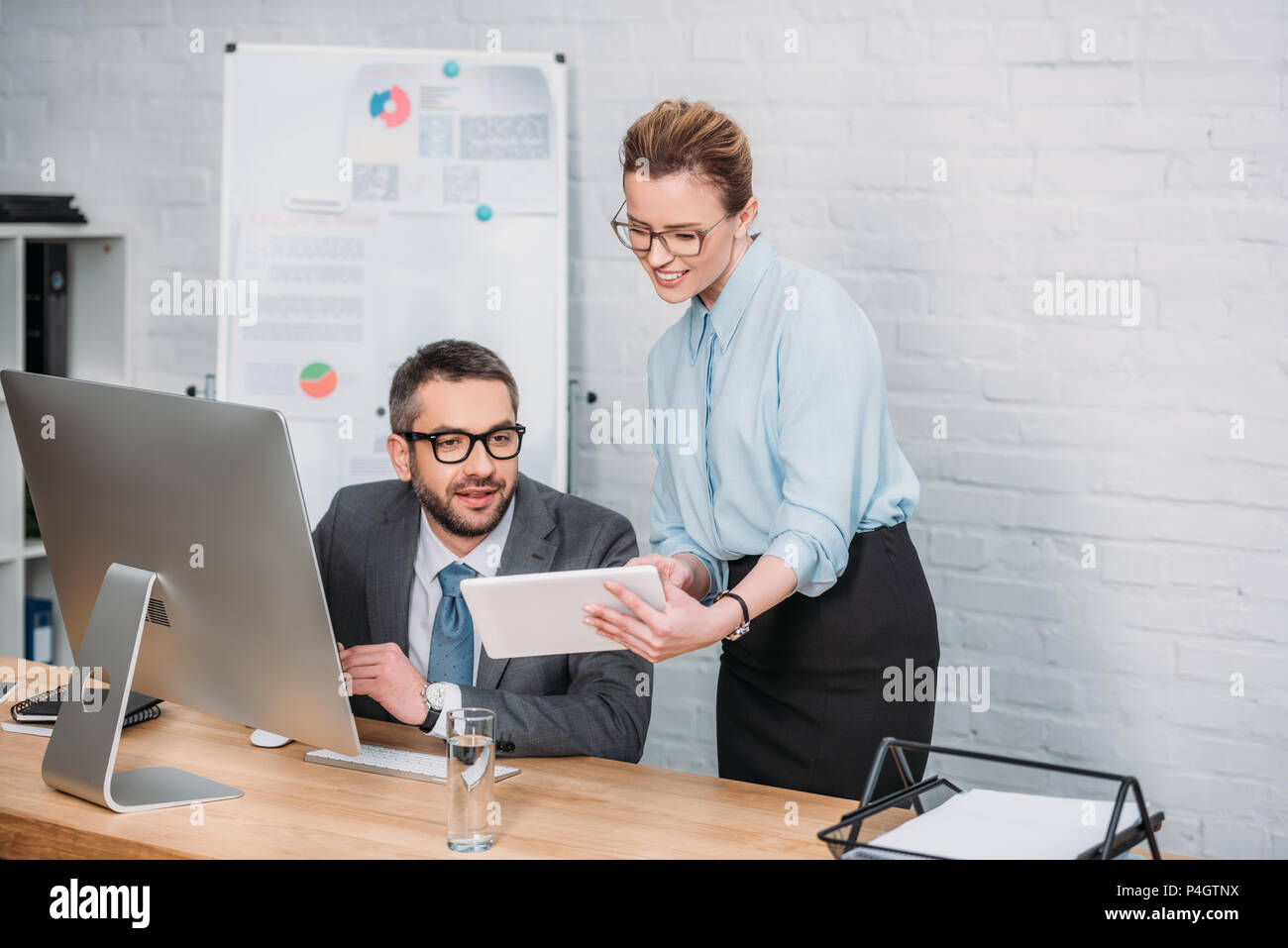 successful modern businesspeople working with digital devices at office - Stock Image
