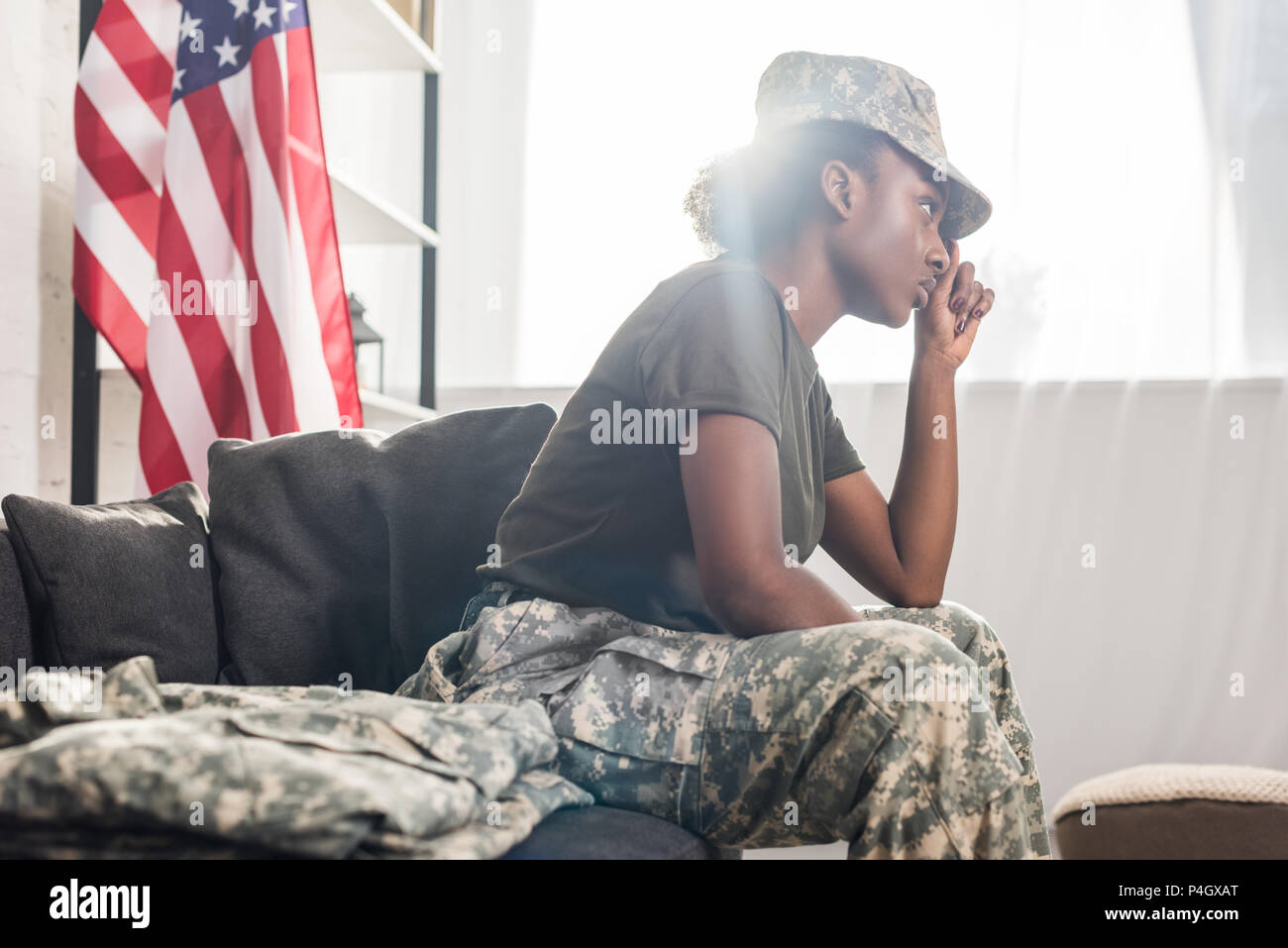 African american female soldier sitting on sofa - Stock Image