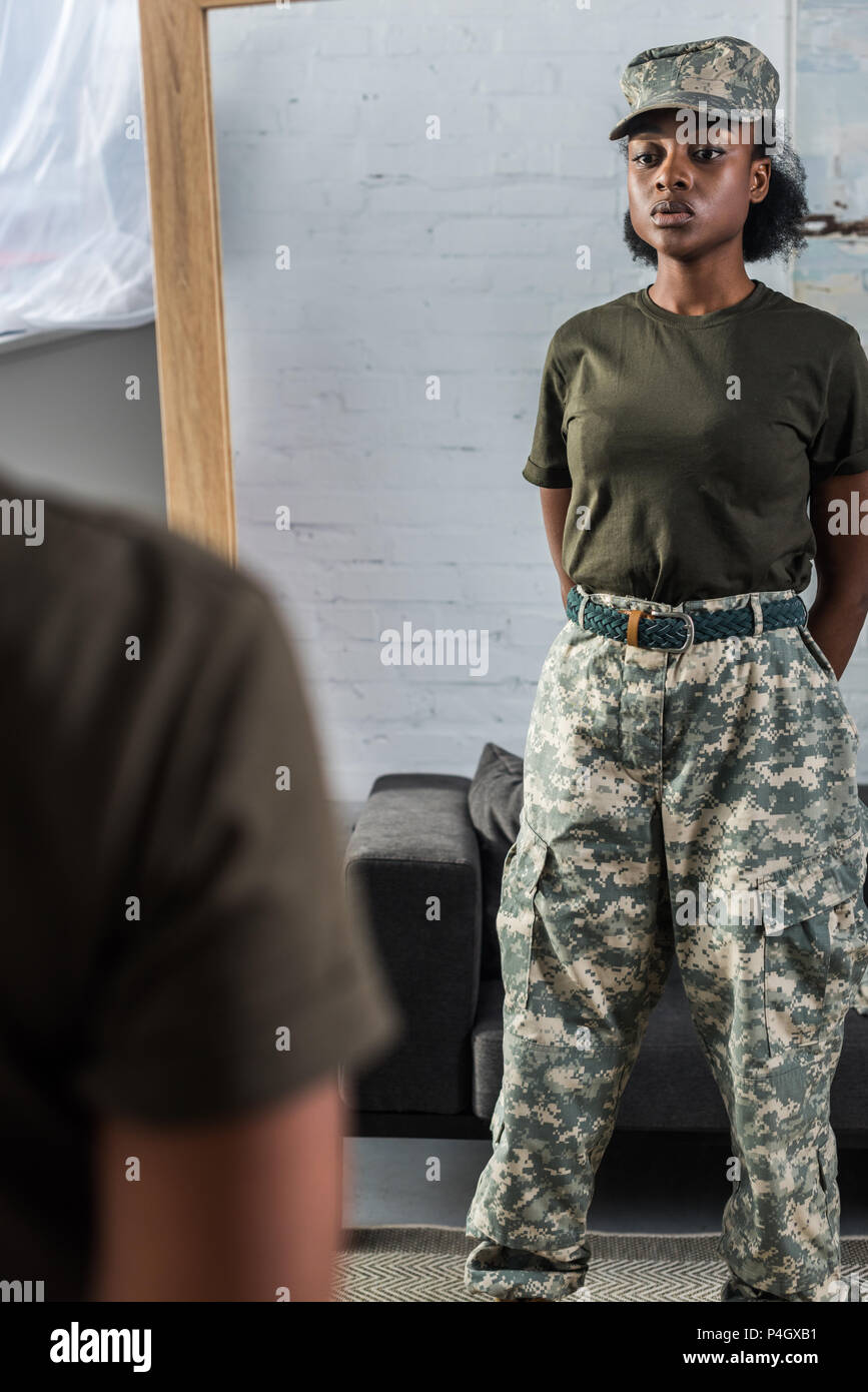 African american female soldier posing by the mirror - Stock Image