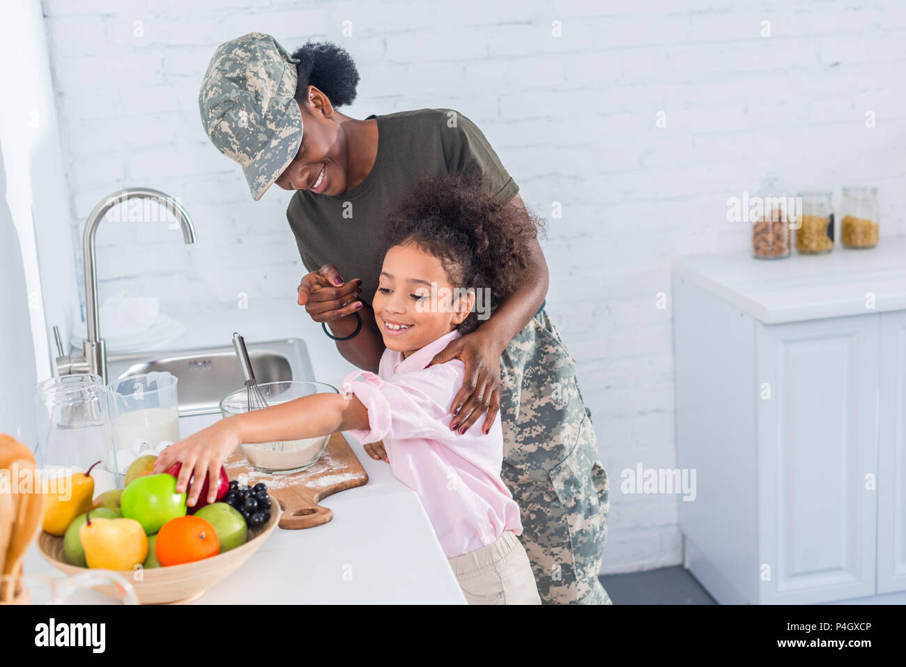 Mother soldier and african american child cooking together - Stock Image