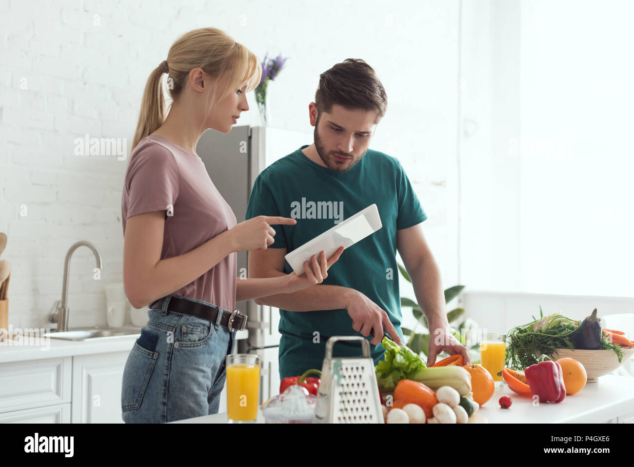 girlfriend pointing on tablet with recipe during cooking at kitchen, vegan concept - Stock Image