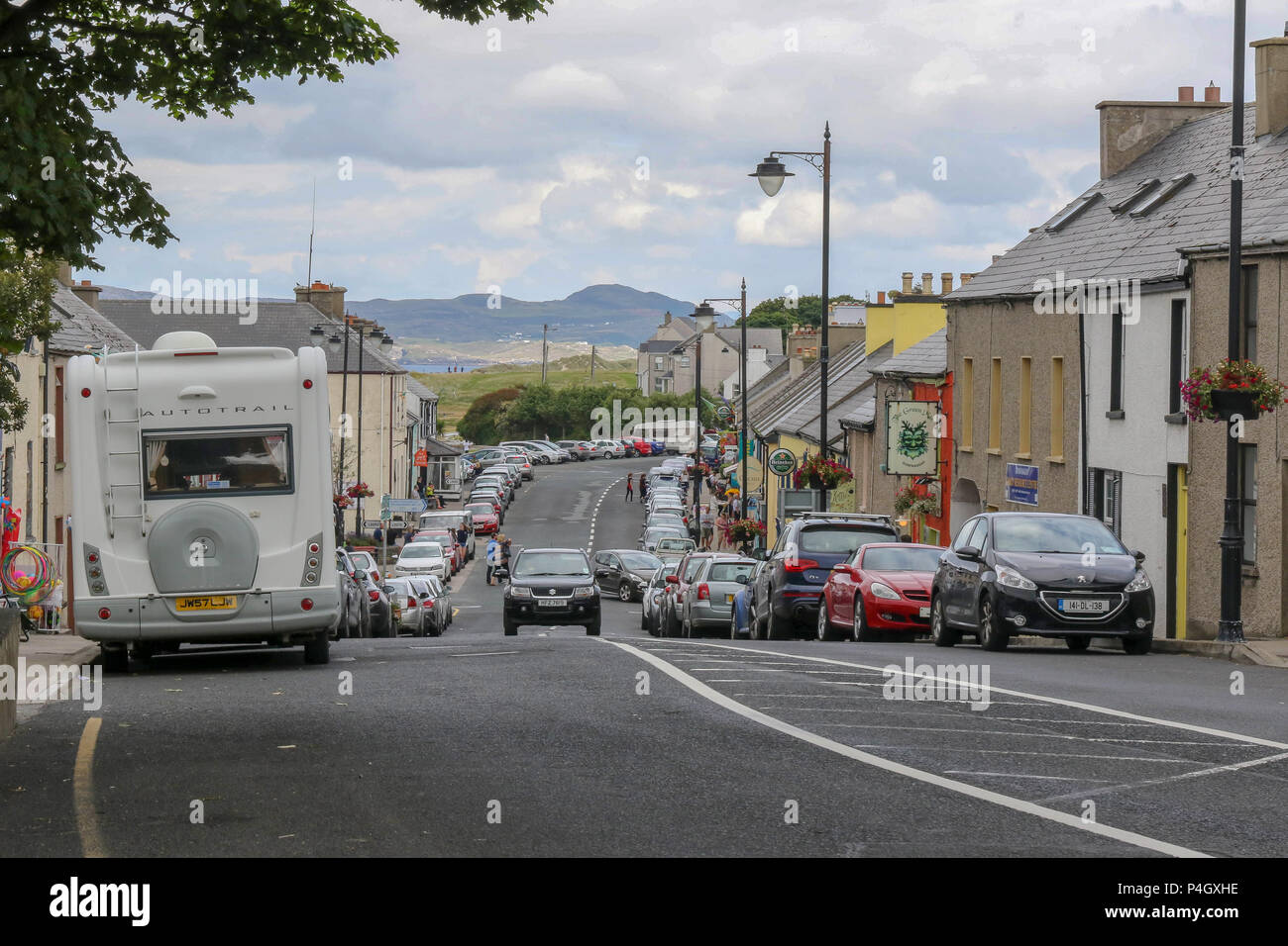Cars and shops in the main street in Dunfanaghy - a popular village for tourists in County Donegal, Ireland. - Stock Image