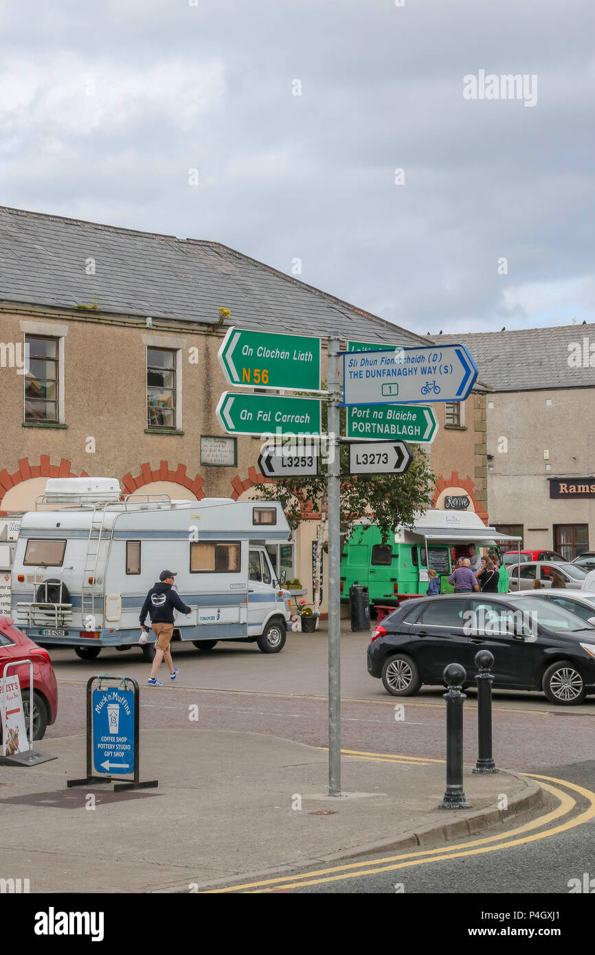 Car park and people in the centre of Dunfanaghy, a popular village in County Donegal. - Stock Image