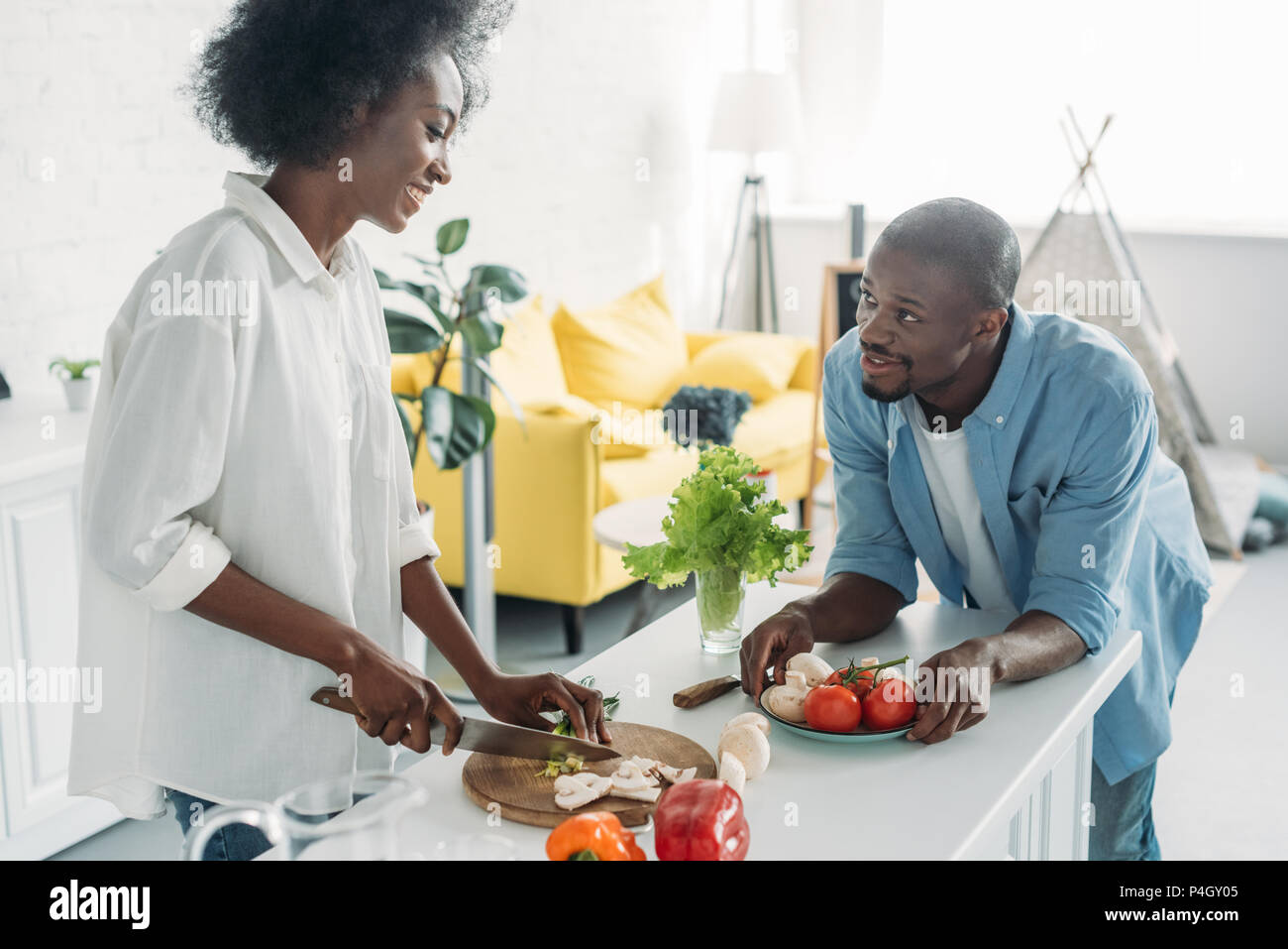 african american man looking at wife cooking breakfast in kitchen at home - Stock Image