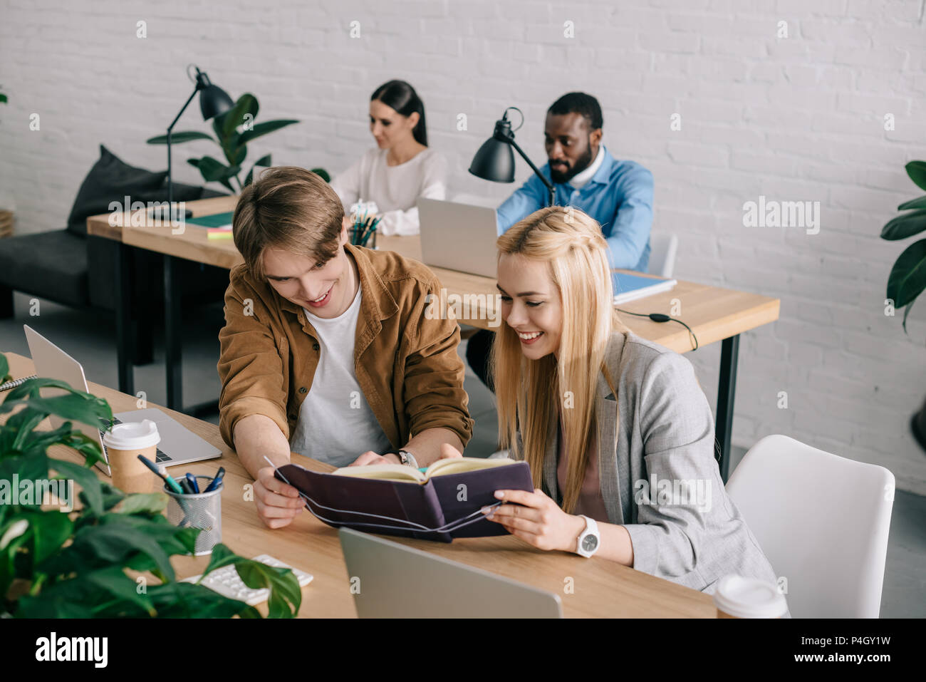 smiling business partners watching on textbook and colleagues sitting behind in office - Stock Image