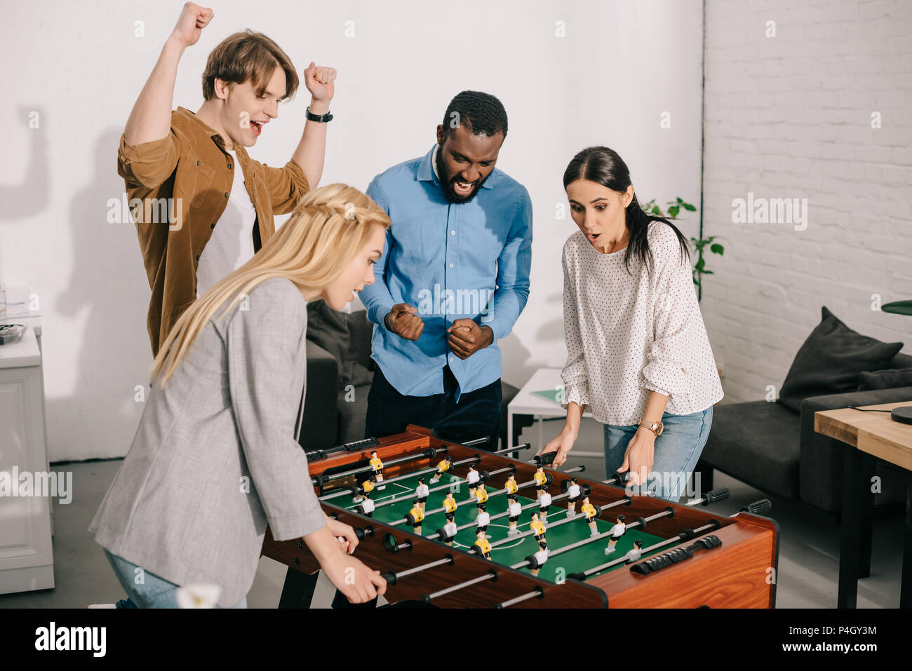 two businesswomen playing table football and male colleagues cheering up  them d84d81bb57