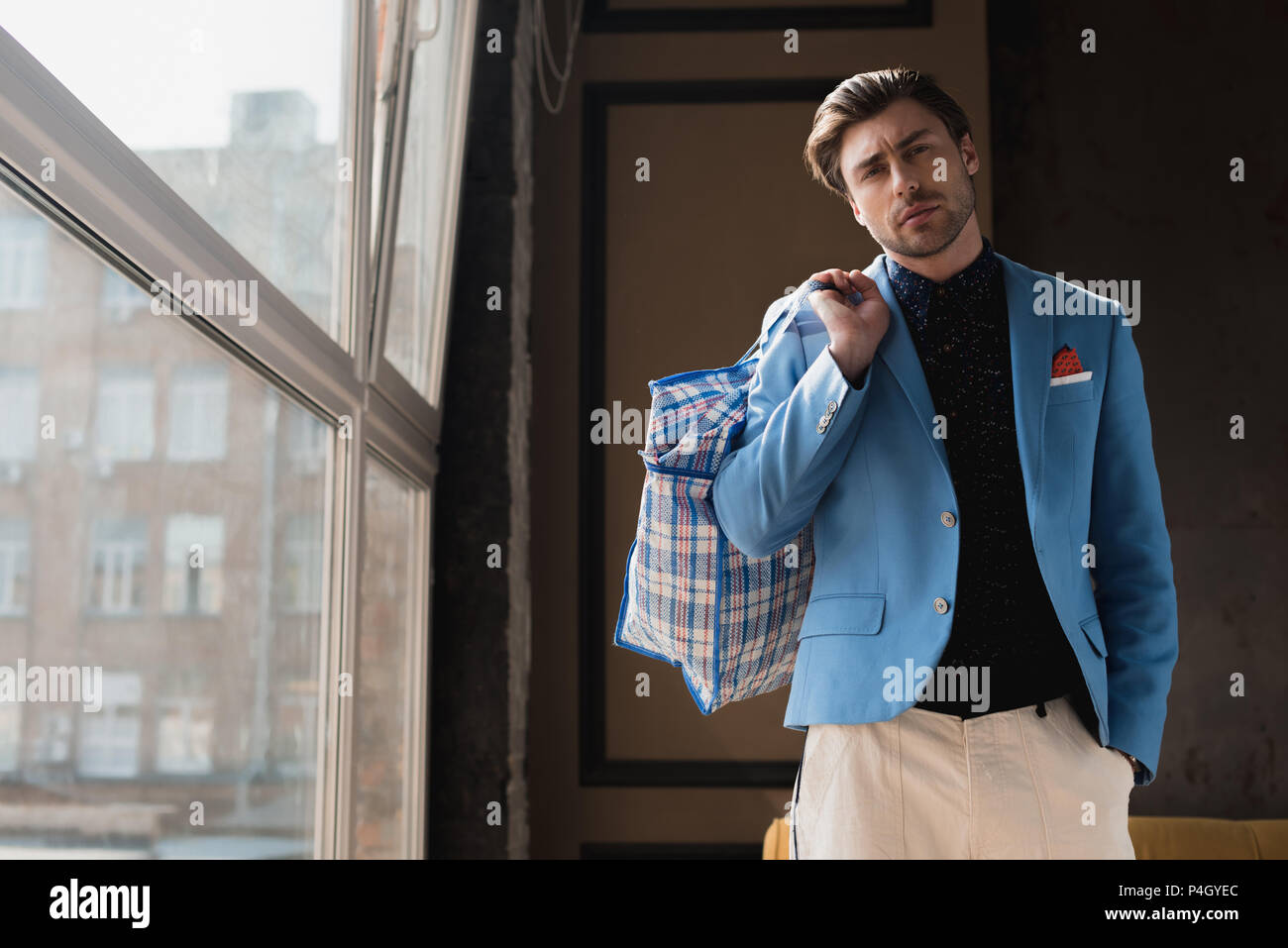 stylish young man with vintage zippered duffle bag on shoulder - Stock Image