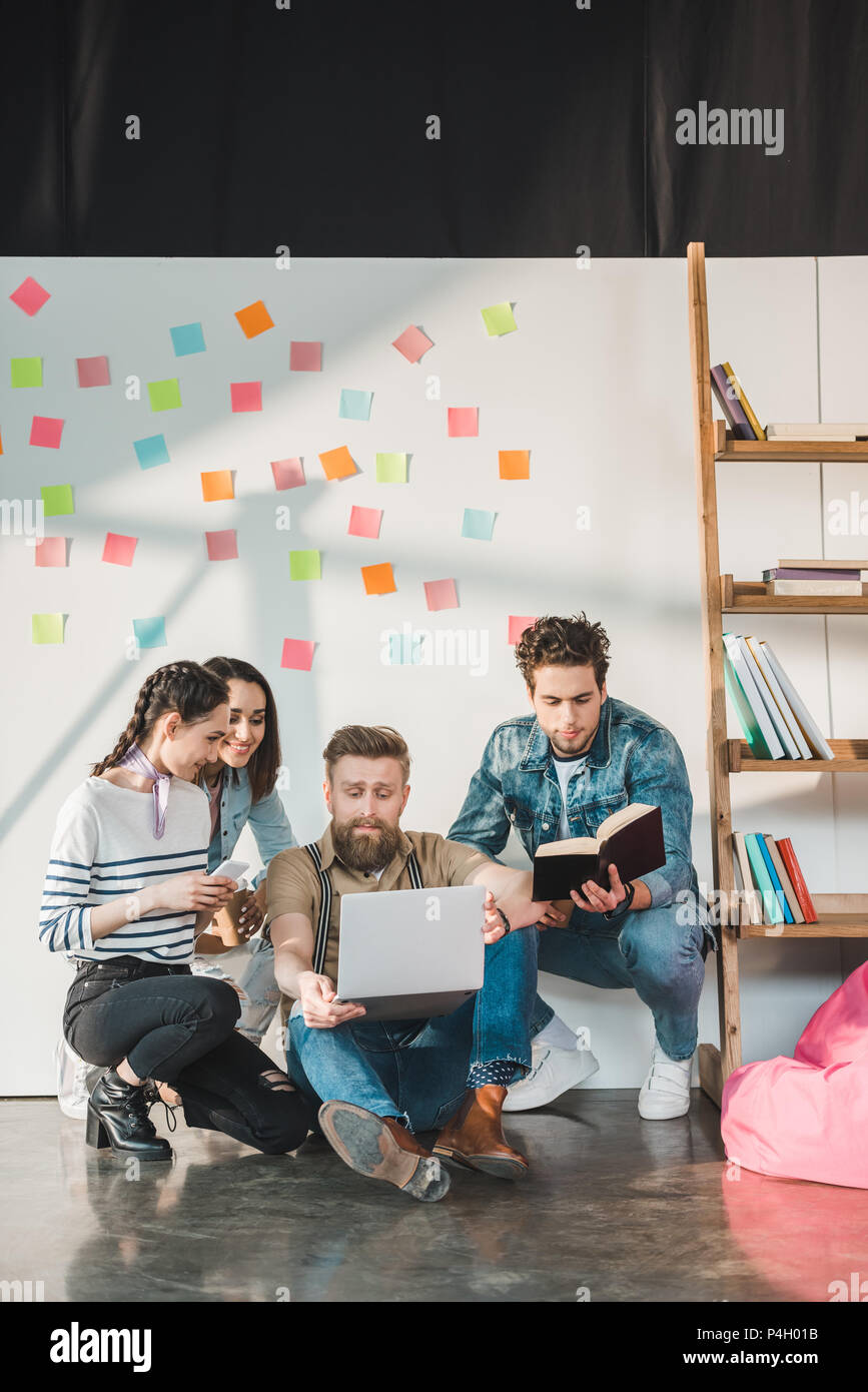 Diverse business team making research on project in light workspace - Stock Image