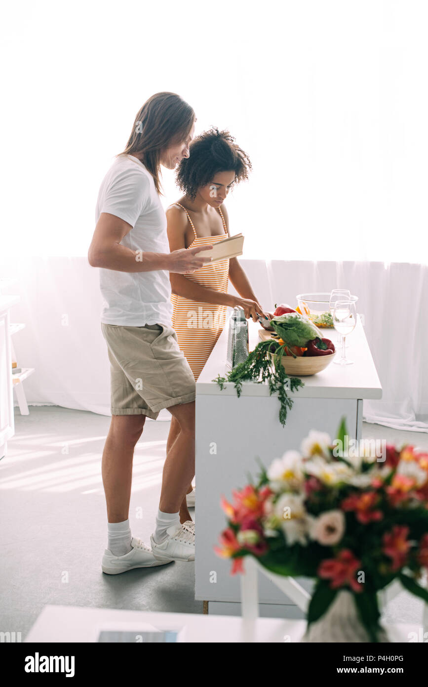 side view of multicultural couple with recipe in book cooking at kitchen Stock Photo
