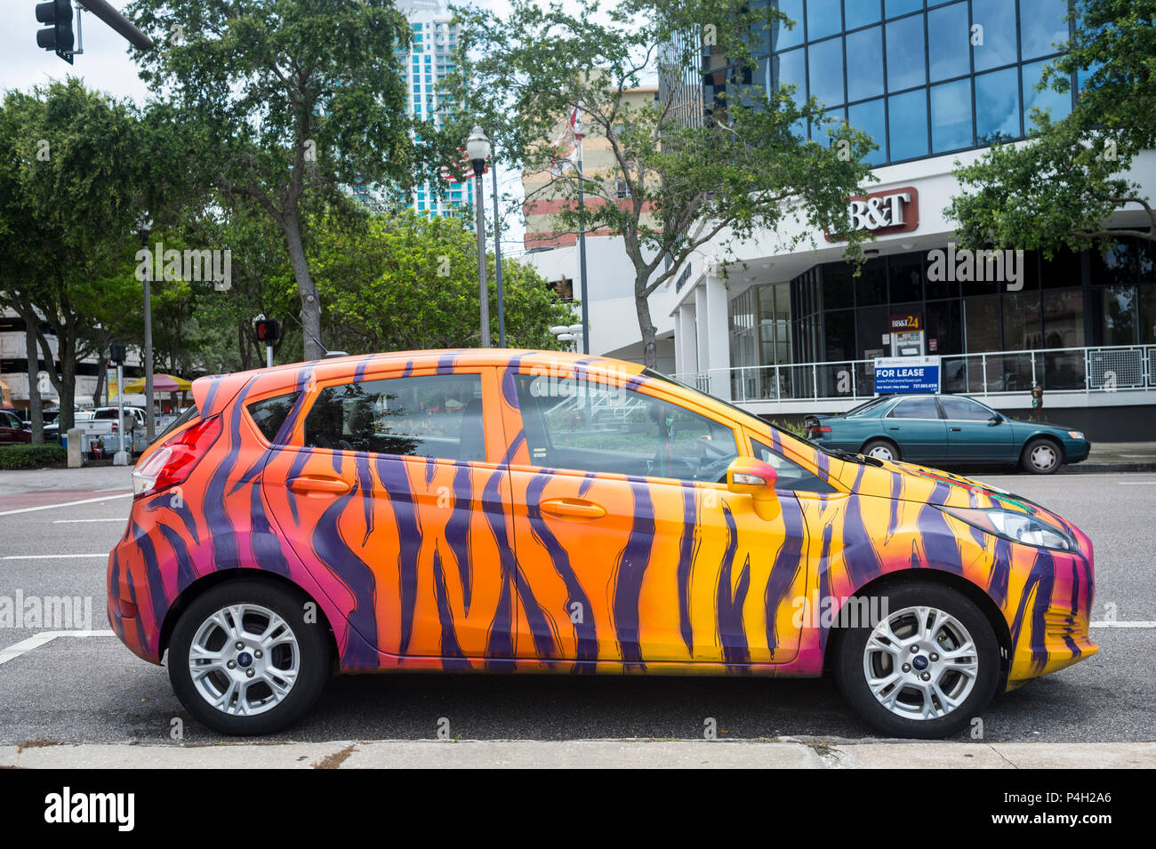 ford car painted in multicoloured striped design. - Stock Image