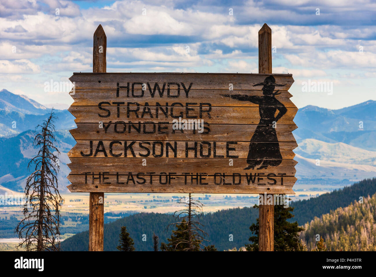Sign at pass through mountains from Idaho to Wyoming, with view of Jackson Hole from 8400 feet. - Stock Image