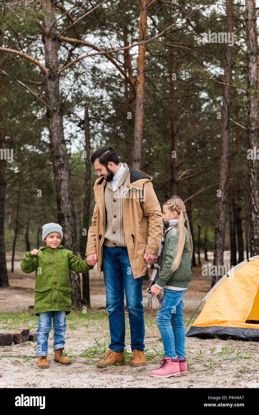 father and little happy kids on hiking trip in pine forest - Stock Image