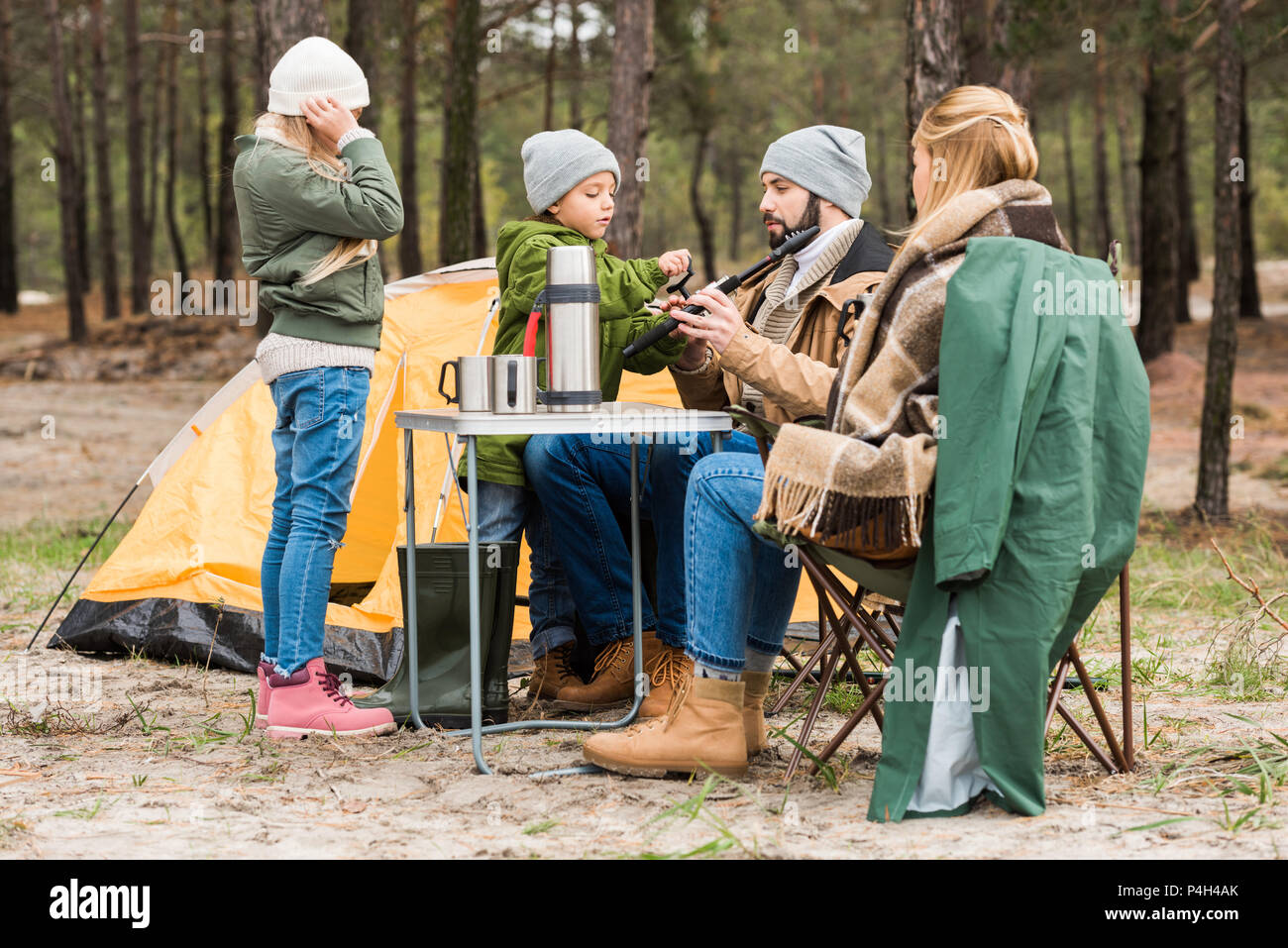 beautiful young family on camping in forest - Stock Image