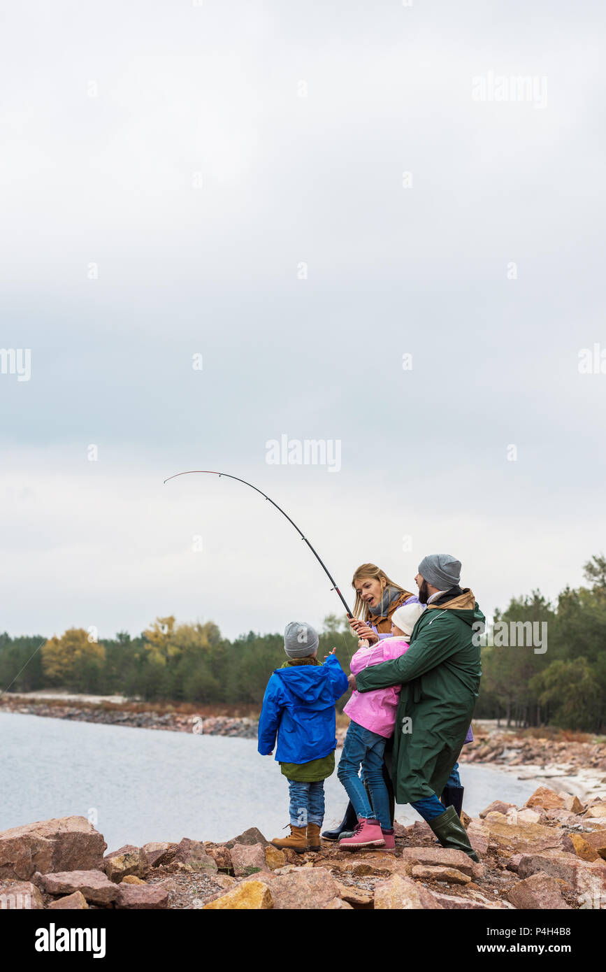 excited young family fishing together at forest lake - Stock Image