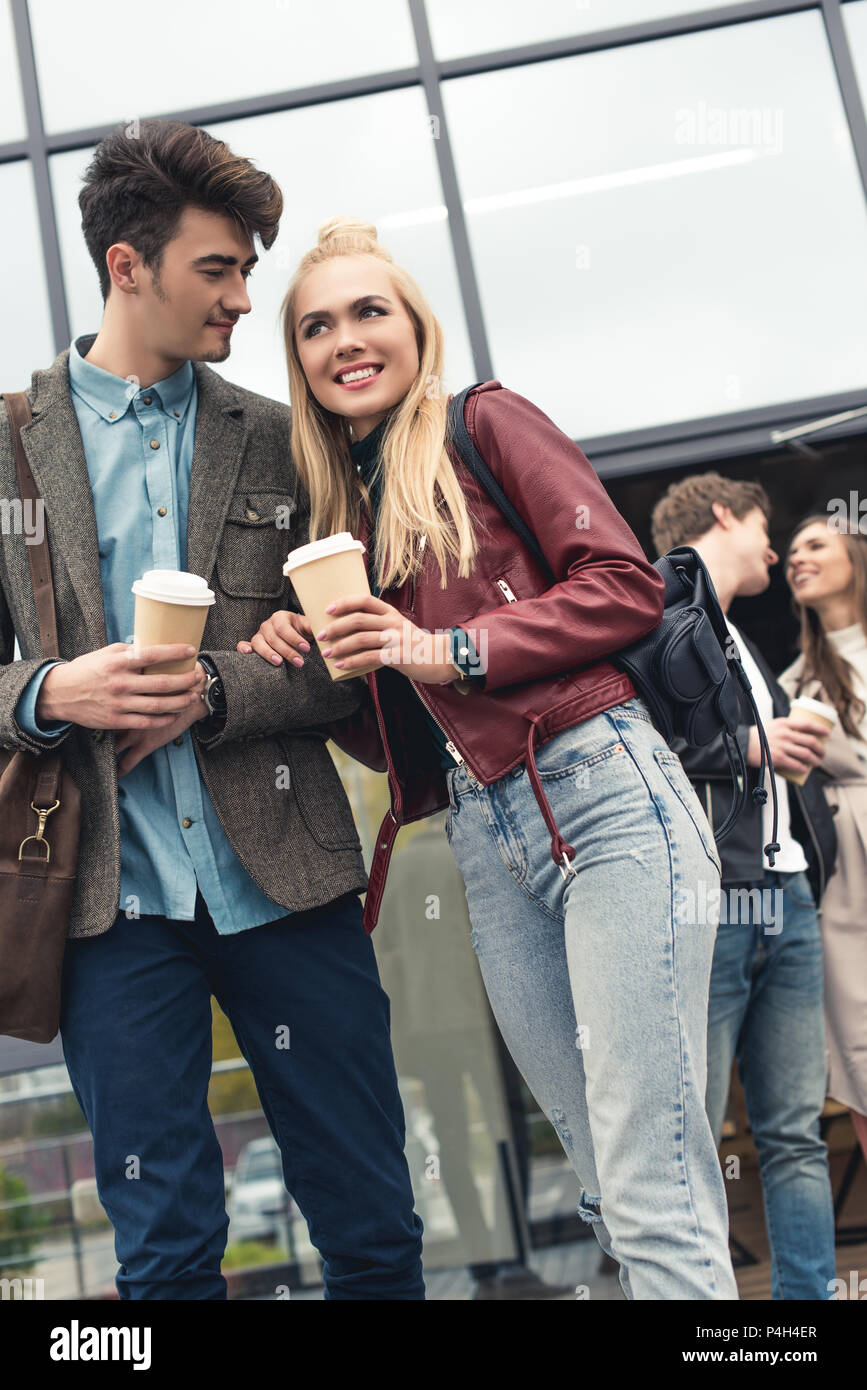Two heterosexual couples going out from building with coffee in paper cups - Stock Image