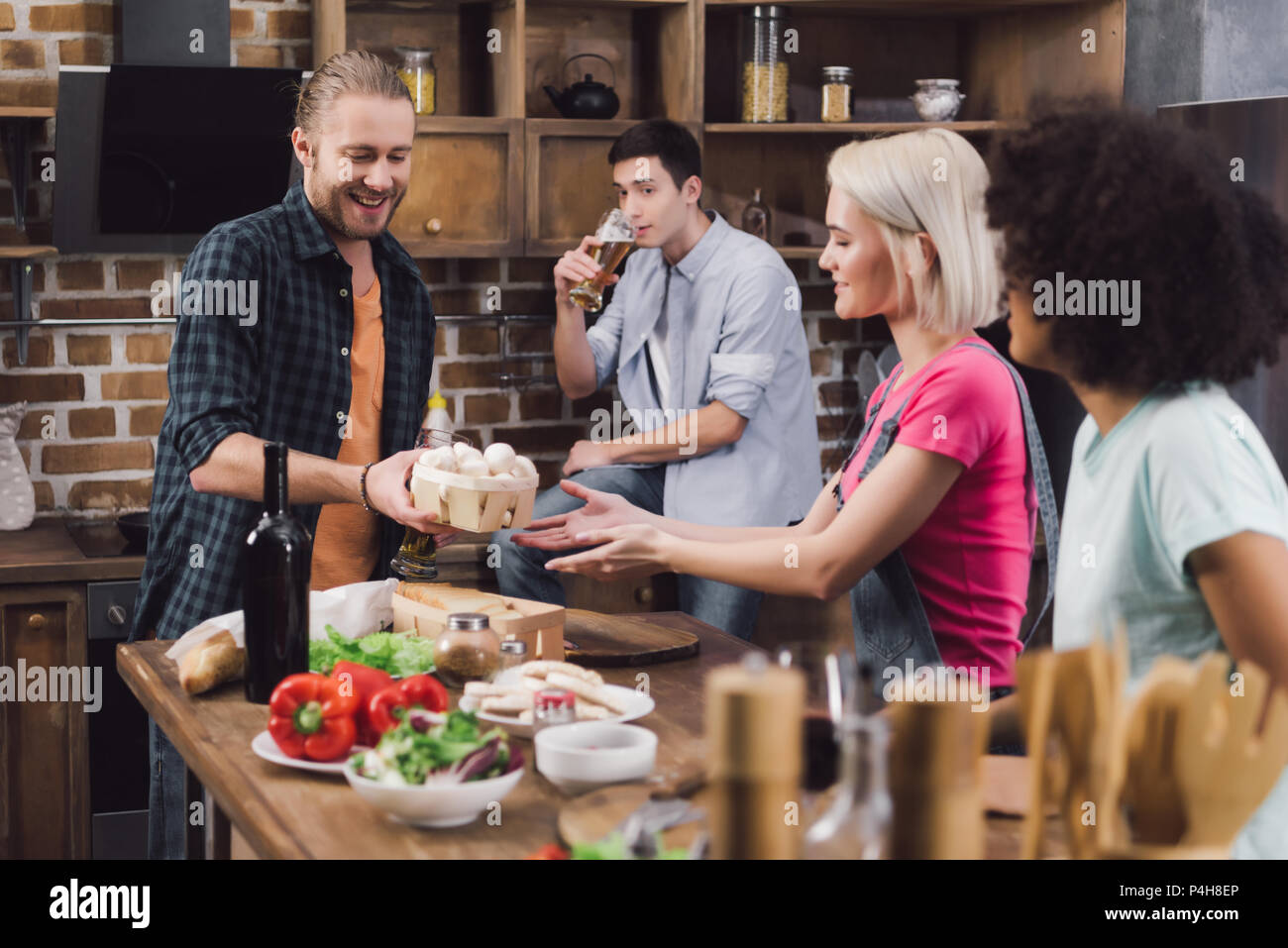 man giving mushrooms to multiethnic friends who cooking - Stock Image
