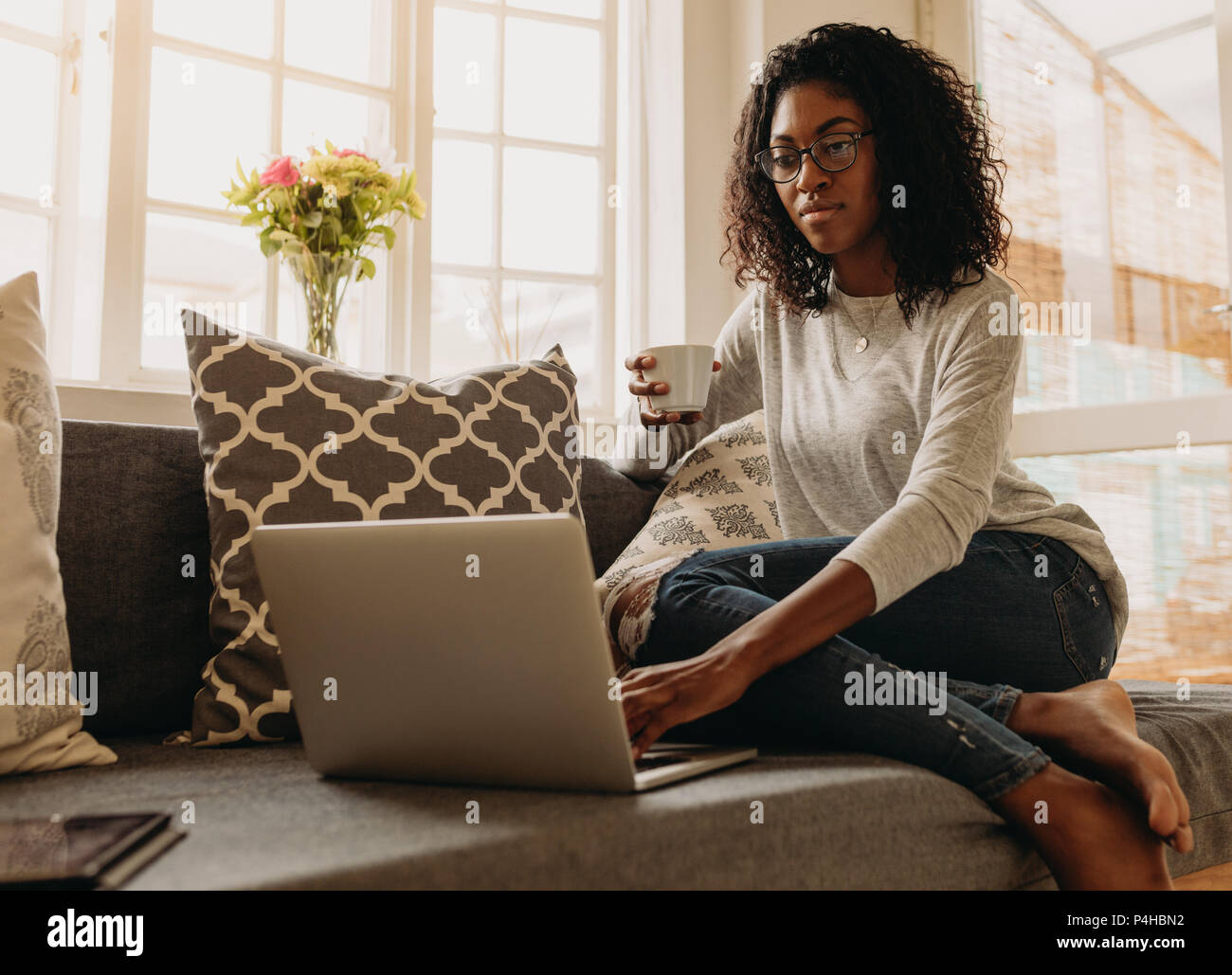Businesswoman working on laptop computer sitting at home holding a coffee cup in hand. Woman sitting on sofa at home and managing her business. - Stock Image
