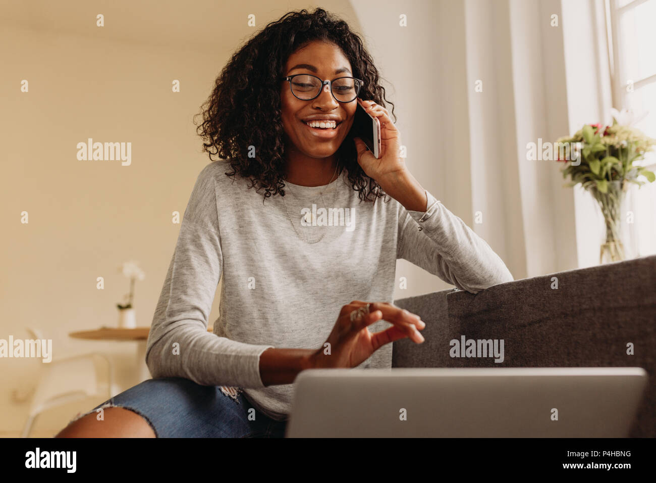 Businesswoman sitting on sofa at home and talking over mobile phone while working on laptop. Smiling woman in fashionable torn jeans working on laptop - Stock Image