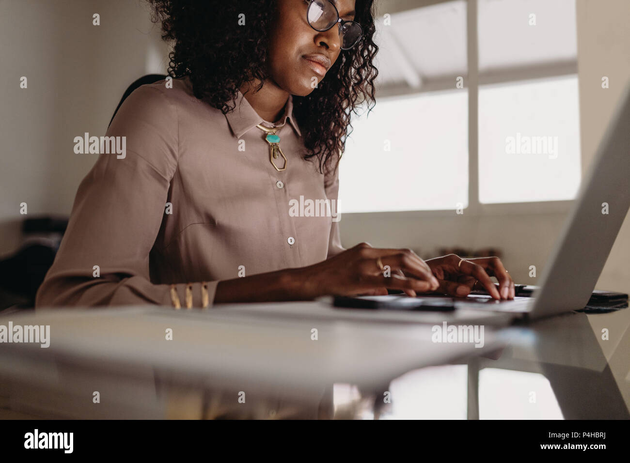 Businesswoman working on laptop computer from home. Woman entrepreneur sitting at home working on laptop with business documents on the table. - Stock Image