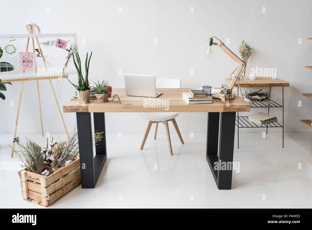 florist workplace with board, dry flowers and laptop in modern office - Stock Image