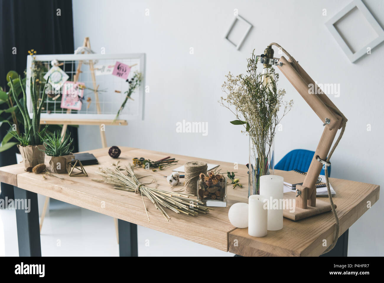 florist workplace with board, dry flowers and wheat ears in modern office - Stock Image