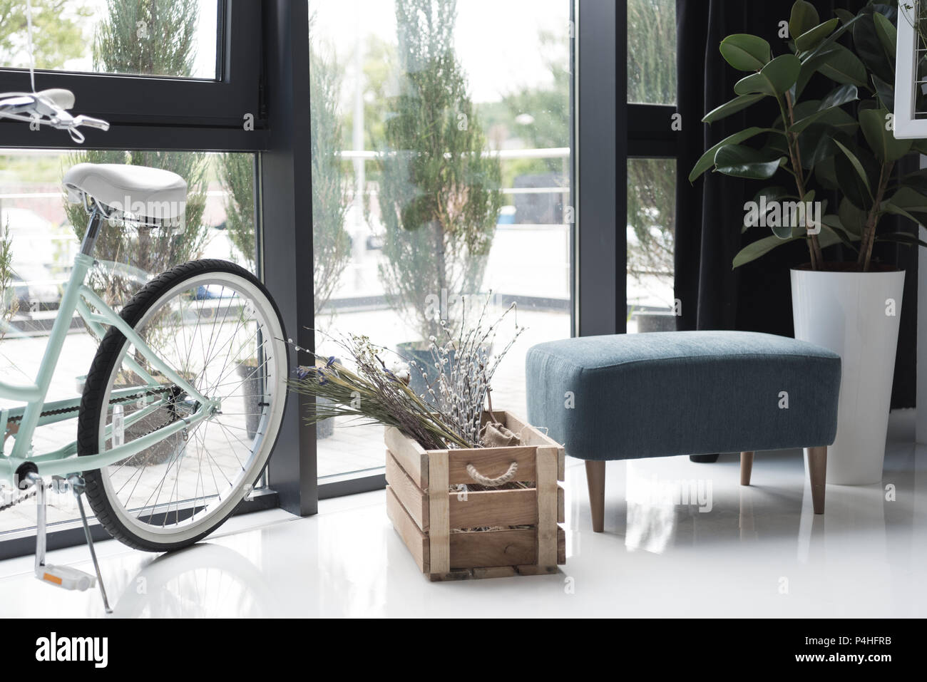 interior of empty creative office with bicycle and dry flowers in wooden box - Stock Image