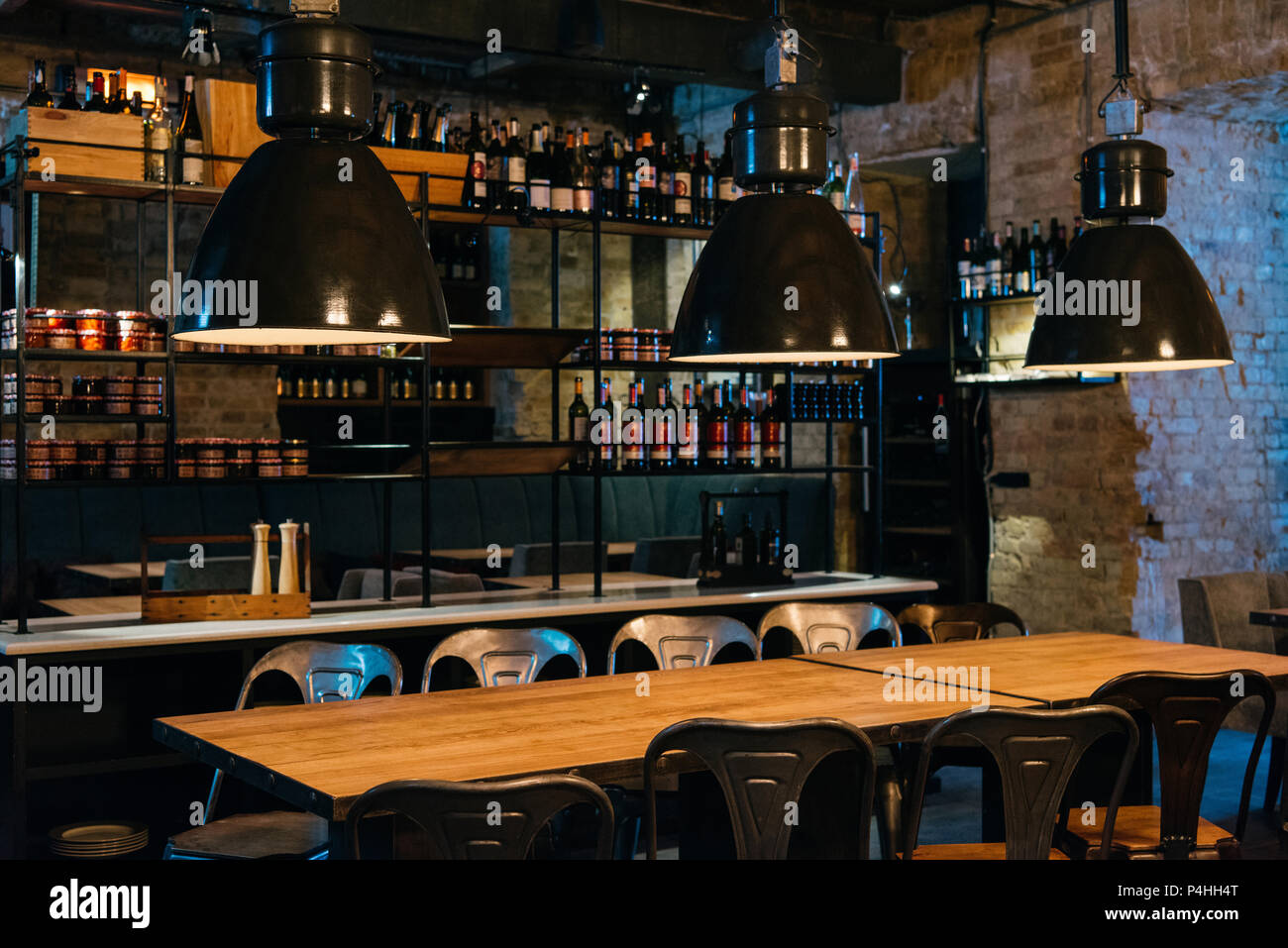 Wooden Tables Lamps And Bar Counter In Modern Restaurant Stock Photo Alamy