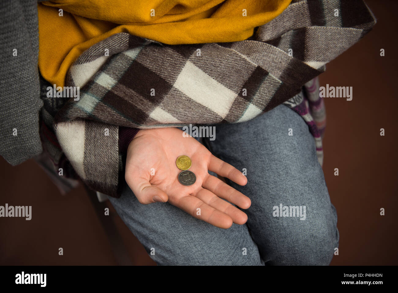 Cropped image of poor man holding coins on hand isolated on brown - Stock Image