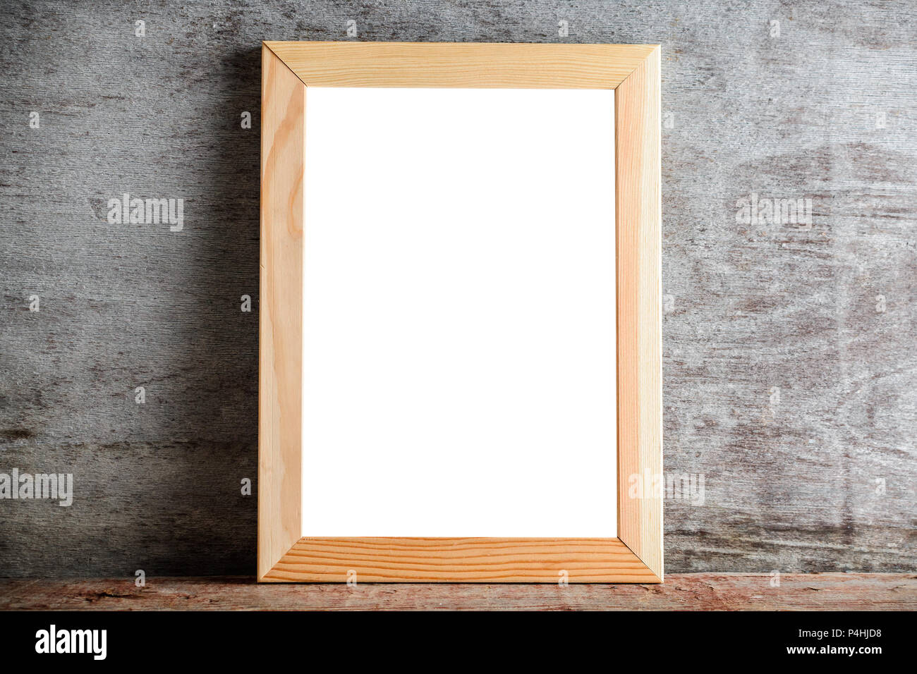 An empty wooden frame on a wooden table on a gray wall. Template ...
