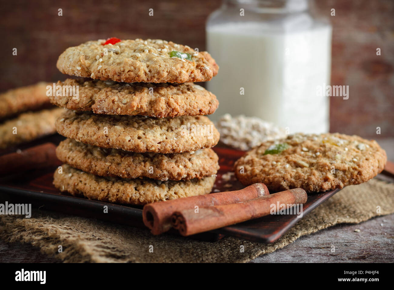 Homemade Oatmeal Cookies Stacked Cinnamon Sticks And A Glass Of