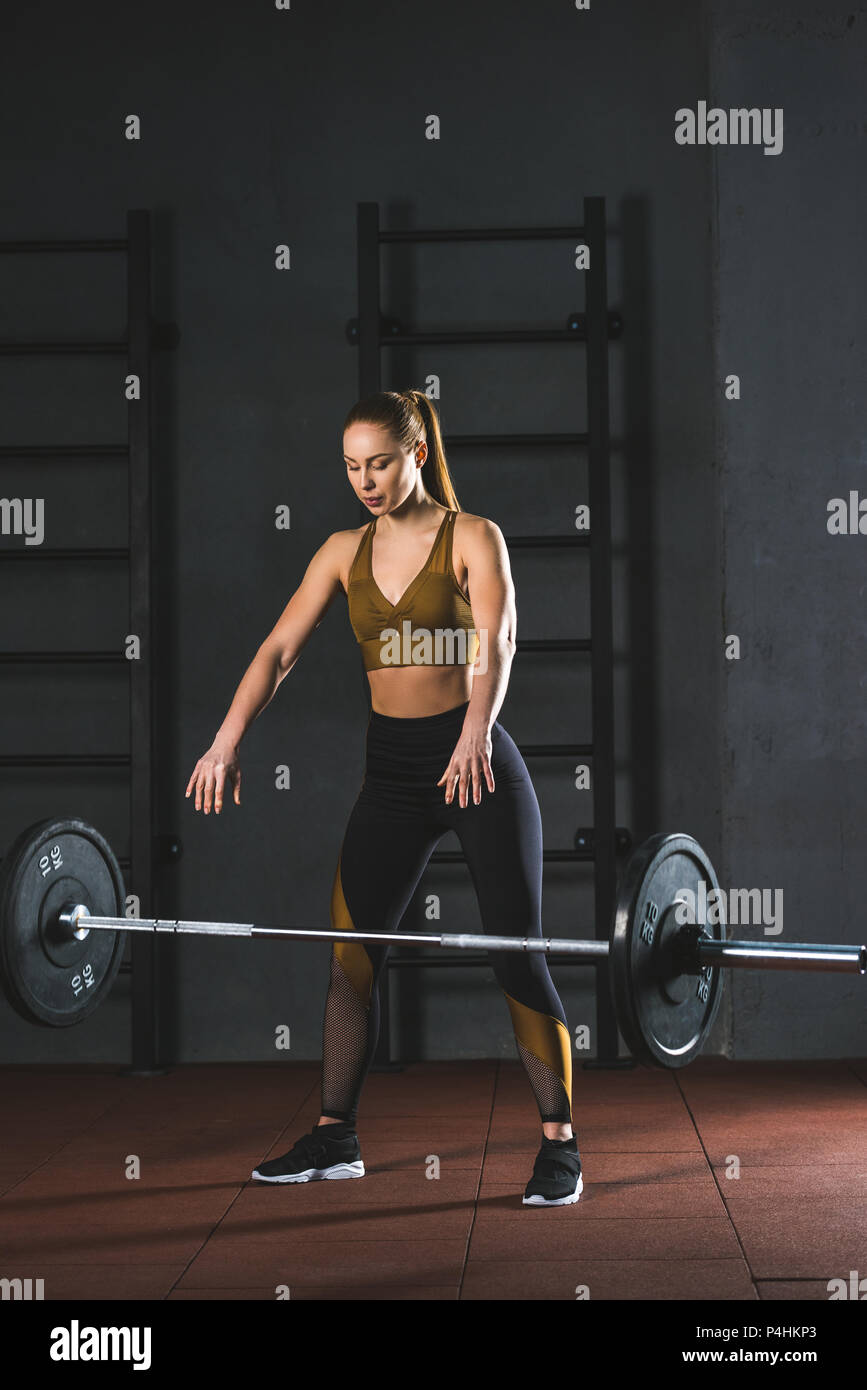 Young caucasian sportswoman letting go barbell  in sports hall - Stock Image