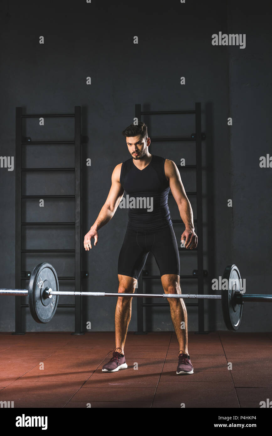Young caucasian sportsman letting go barbell in sports hall - Stock Image