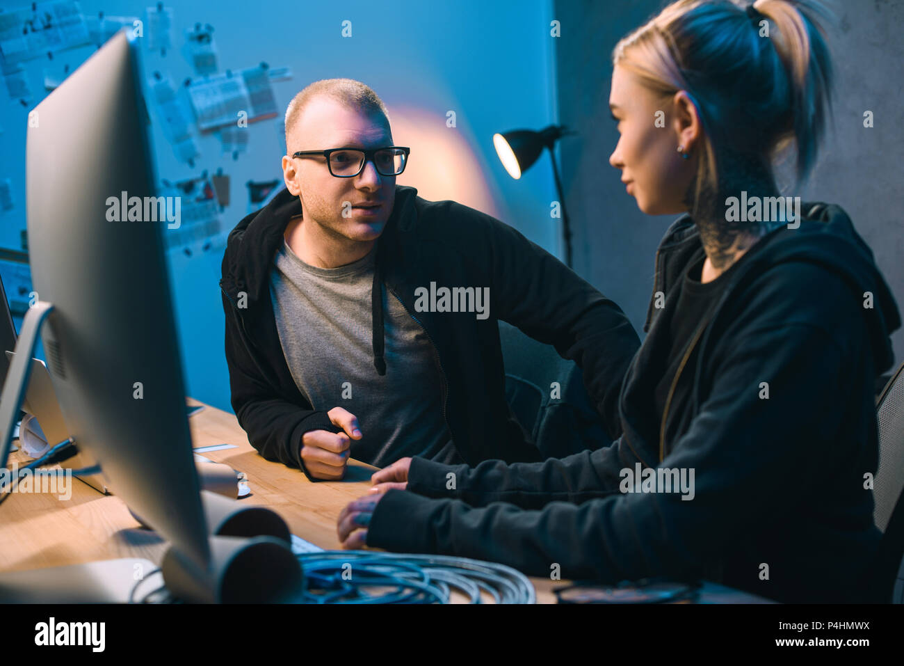 couple of hackers chatting at workplace in dark room - Stock Image